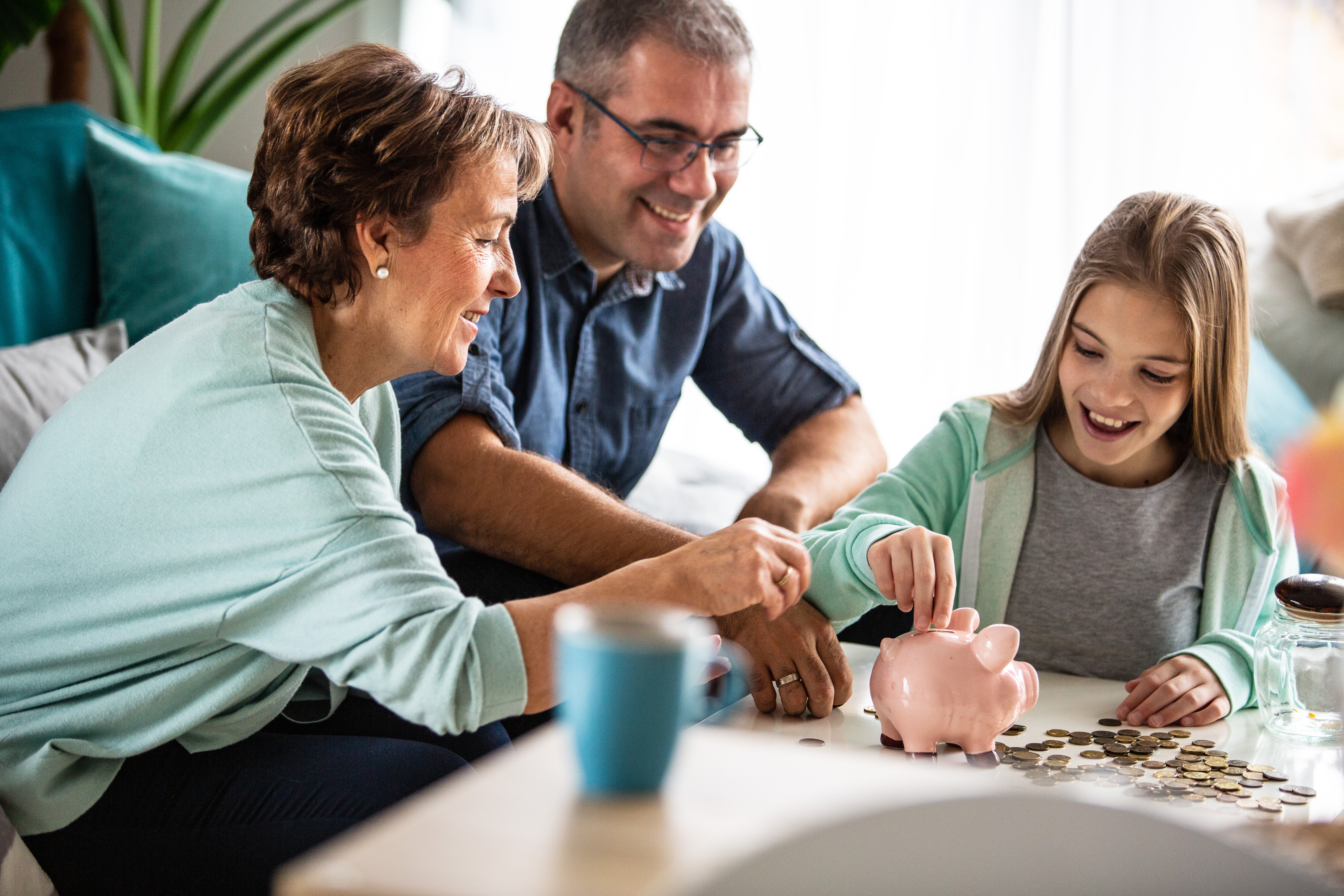 Gramma, Father and daughter all counting money with piggy bank on the table