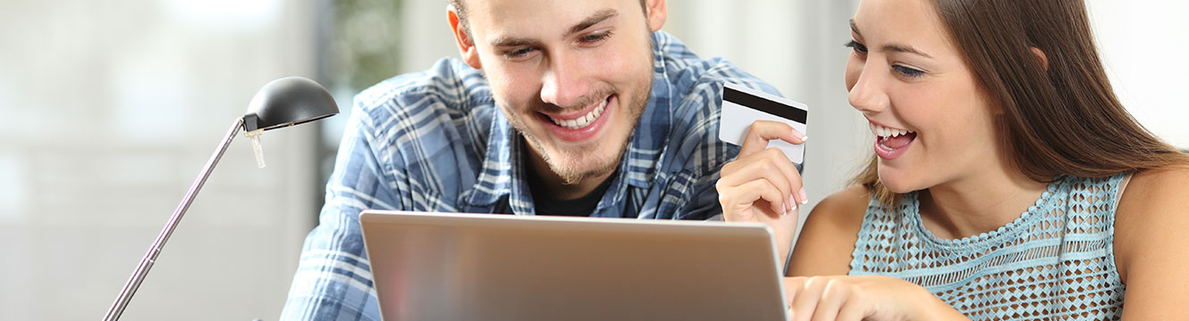 Male and female in their mid-20s smiling at computer while female holds credit card in her hand