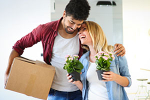 Smiling man holding box while hugging girl holding two plants, laughing at man
